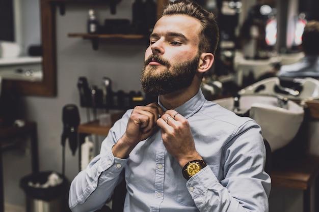 Hombre abotonando la camisa en la barbería Foto gratis