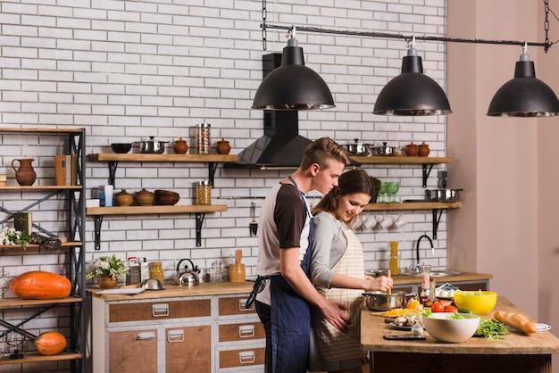 Hombre abrazando a la mujer mientras cocinan juntos Foto gratis
