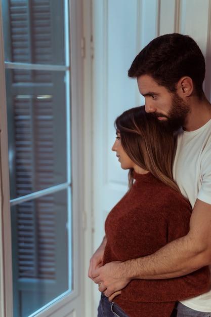 Hombre, abrazar, mujer, cerca de ventana Foto gratis