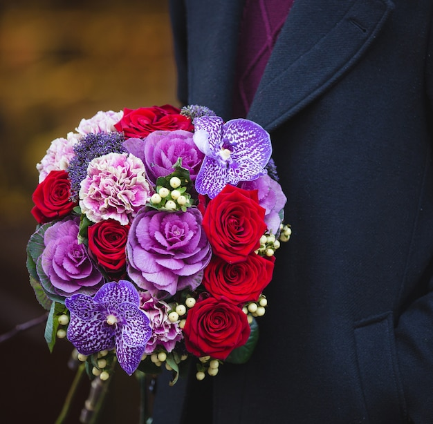 Hombre en abrigo con un ramo de flores mixtas rojo y púrpura. Foto gratis
