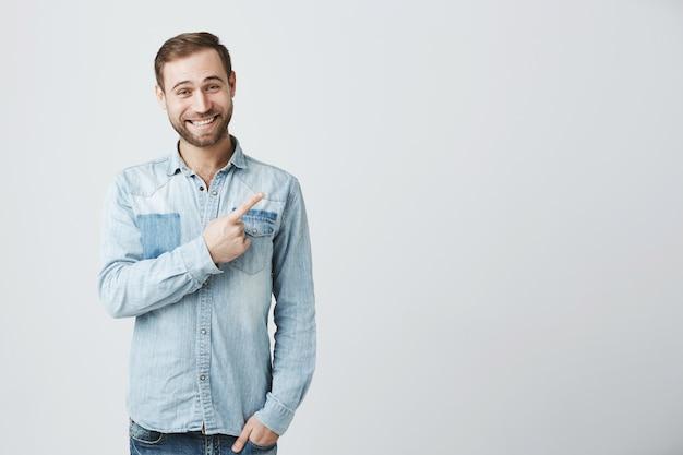 Hombre acertado sonriente que señala el dedo esquina superior derecha contento Foto gratis