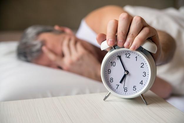 Hombre acostado en la cama apagar un despertador en la mañana a las 7 am. atractivo hombre durmiendo en su dormitorio. hombre molesto despertado por un despertador en su dormitorio Foto gratis