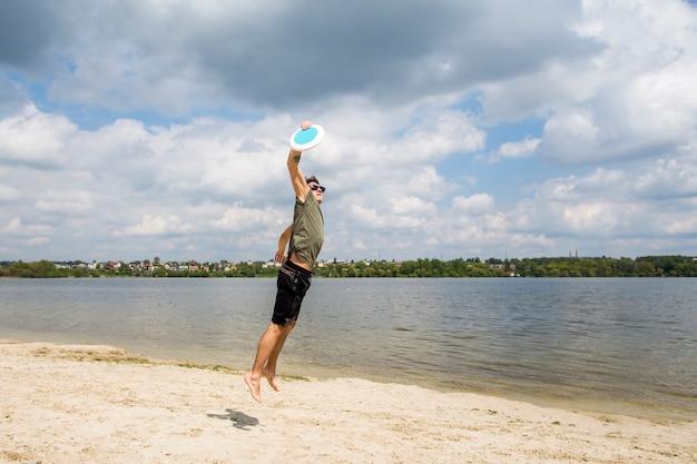 Hombre activo jugando frisbee en playa de arena Foto gratis
