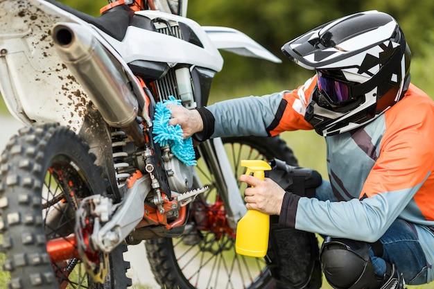 Hombre activo limpiando moto al aire libre Foto gratis