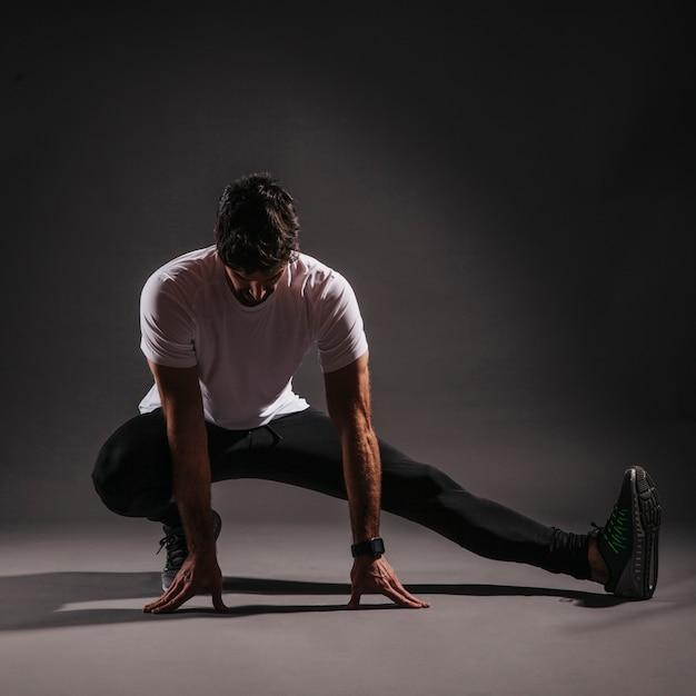 Hombre adulto calentando sobre fondo oscuro | Descargar Fotos gratis