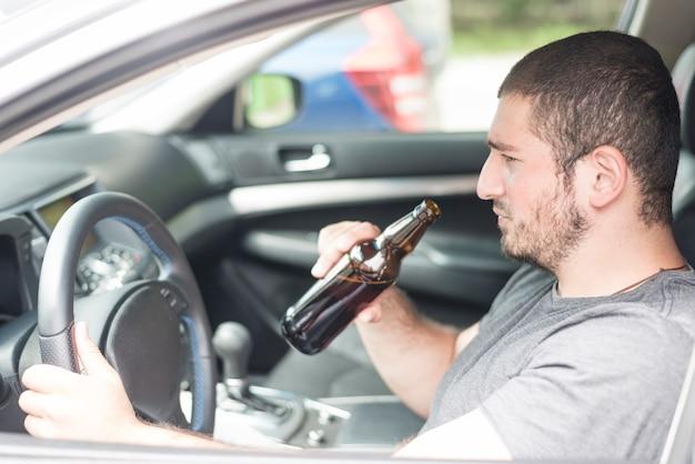 Hombre adulto con cerveza conduciendo coche Foto gratis