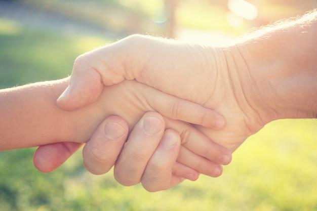 Un hombre adulto da la mano a un niño. el concepto de salvación y asistencia.