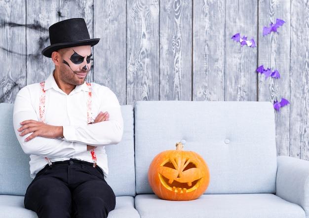 Hombre adulto mirando calabaza de halloween Foto gratis