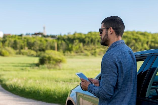 Hombre adulto de pie cerca del coche y usando tableta Foto gratis