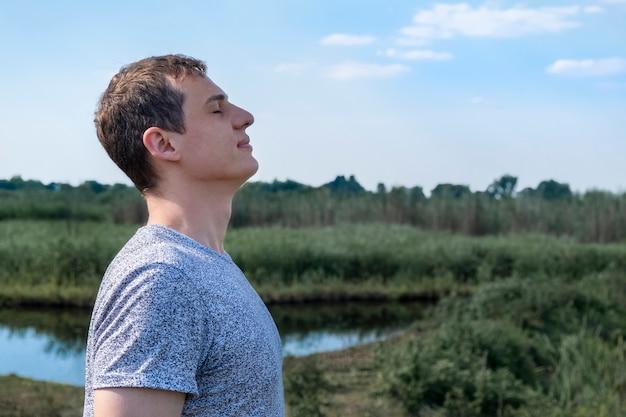 Hombre adulto relajado respirando aire fresco al aire libre con el lago y el campo en el fondo Foto Premium