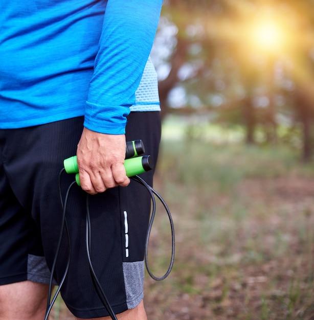 Hombre adulto en ropa azul que sostiene una cuerda de saltar para practicar deportes, de pie de lado Foto Premium