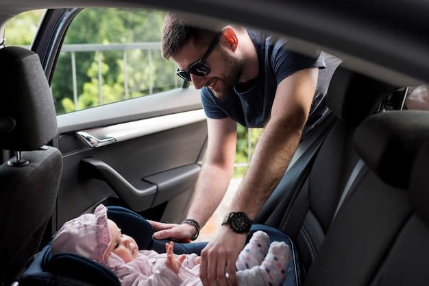 Hombre adulto sacando al bebé de un asiento de seguridad infantil Foto Premium