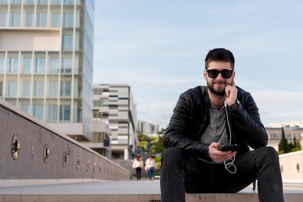 Hombre adulto sentado en el pavimento con teléfono inteligente en la mano Foto gratis