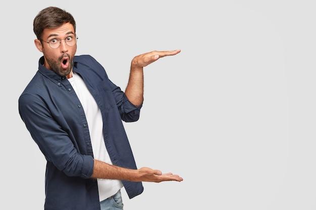 Hombre sin afeitar aturdido con gestos de expresión facial de sorpresa con las manos, muestra el tamaño o la altura de algo, vestido con una camisa de moda, aislado sobre una pared blanca, copyspace Foto gratis