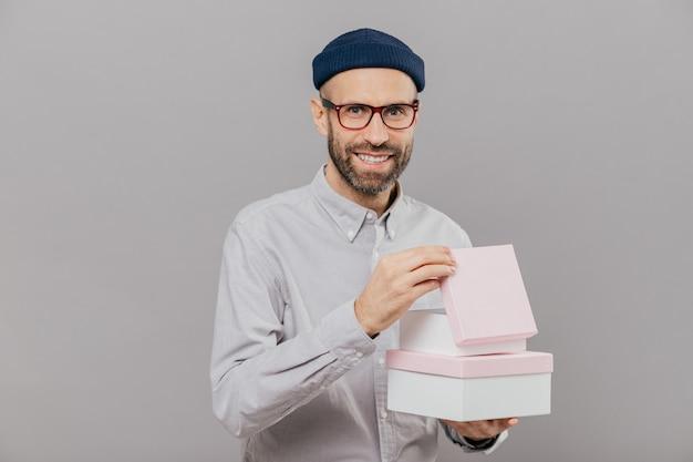 El hombre sin afeitar positivo tiene rastrojos, lleva cajas con regalos, abre uno de ellos Foto Premium