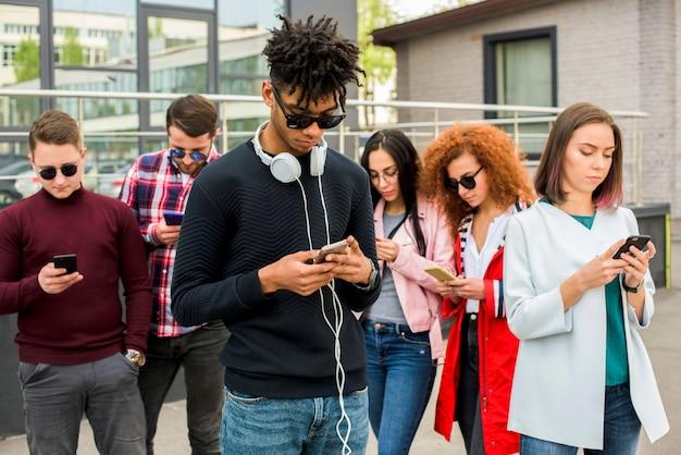 Hombre africano joven que se coloca delante de sus amigos que usan los teléfonos móviles Foto gratis