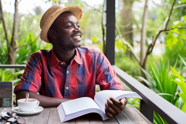 Hombre africano leyendo un libro con café, llave, teléfono inteligente y fondo verde natural. Foto Premium