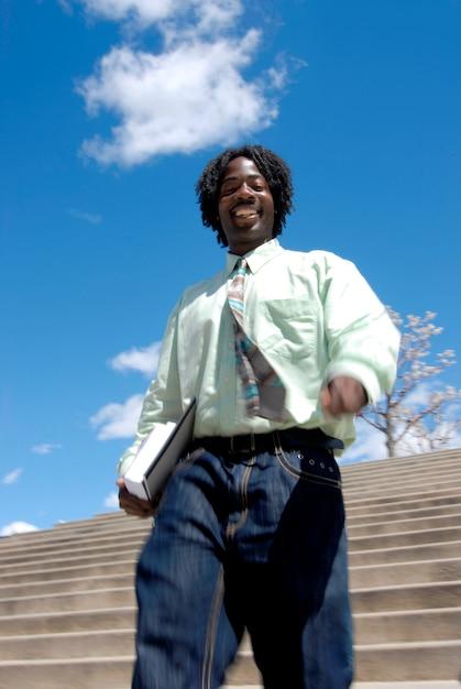 Hombre africano con rastas sonriendo con confianza y descendiendo escalera llevando libros Foto Premium