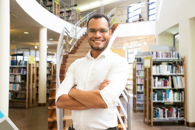 Hombre afroamericano sonriente que presenta en la biblioteca pública Foto gratis