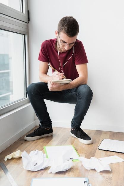 Hombre agachado y apoyado en una pared blanca escribiendo Foto gratis