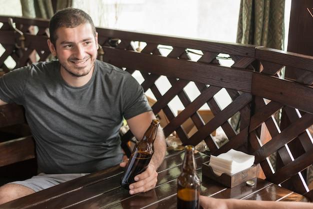 Hombre alegre bebiendo cerveza con un amigo en el bar Foto gratis