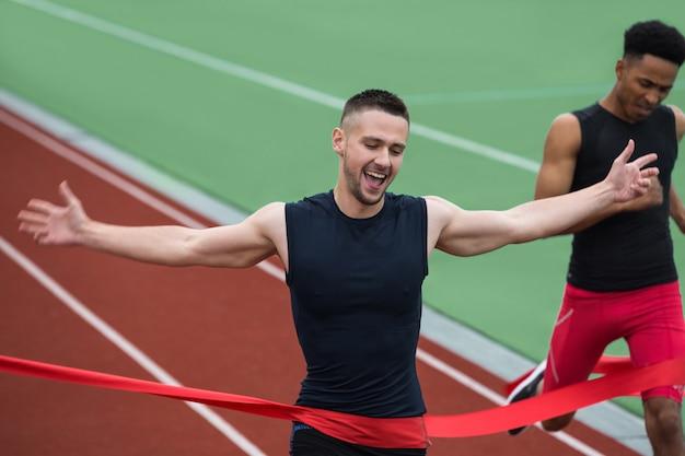 Hombre alegre joven atleta cruzando la línea de meta Foto gratis