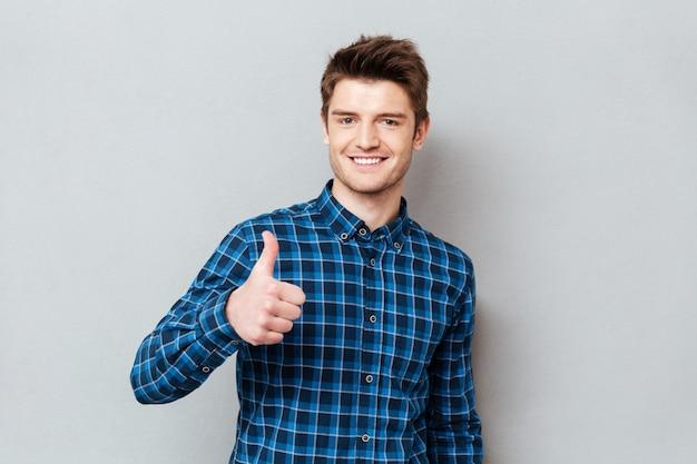 Hombre alegre joven estudiante sosteniendo pulgar aislado Foto gratis