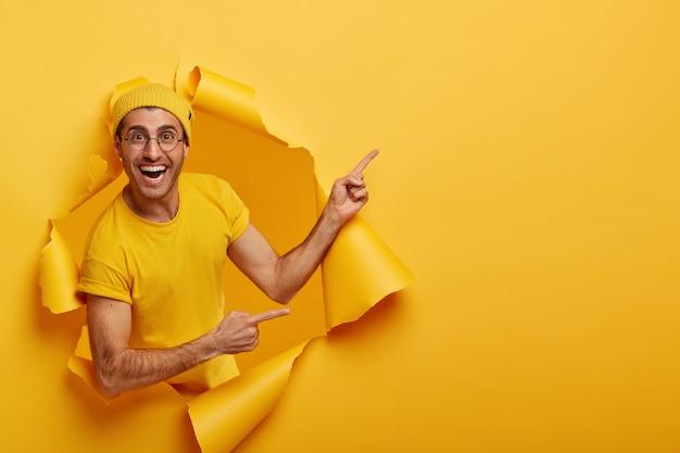Hombre alegre ofrece una buena oferta, anuncia un nuevo producto a la venta, se para en un agujero de papel rasgado, tiene una expresión positiva Foto gratis