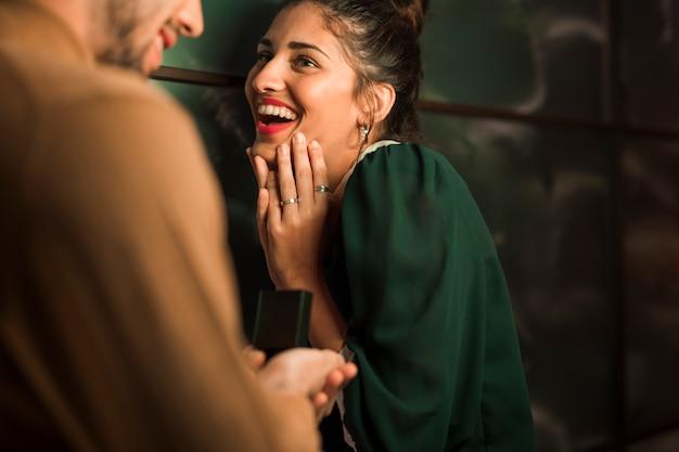 Hombre alegre que presenta el regalo en caja a la mujer feliz joven Foto gratis