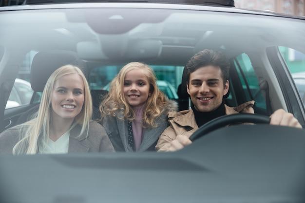 Hombre alegre sentado en coche con su esposa e hija Foto gratis