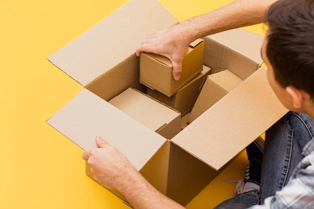 Hombre de alto ángulo arreglando paquetes de entrega Foto gratis