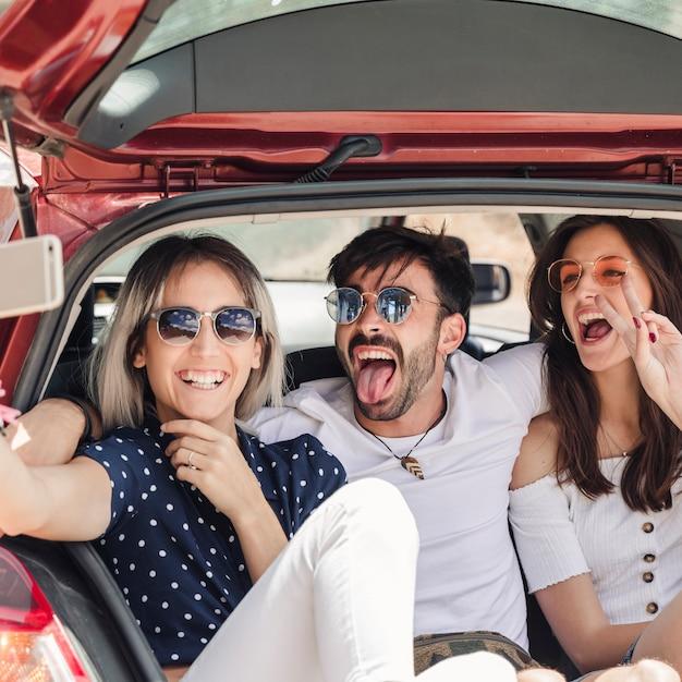 Hombre con amigas sentada en el carro del coche posando para autorretrato Foto gratis