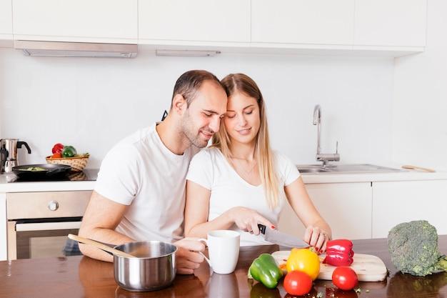 Hombre amoroso sentado con su esposa cortando las verduras con un cuchillo Foto gratis