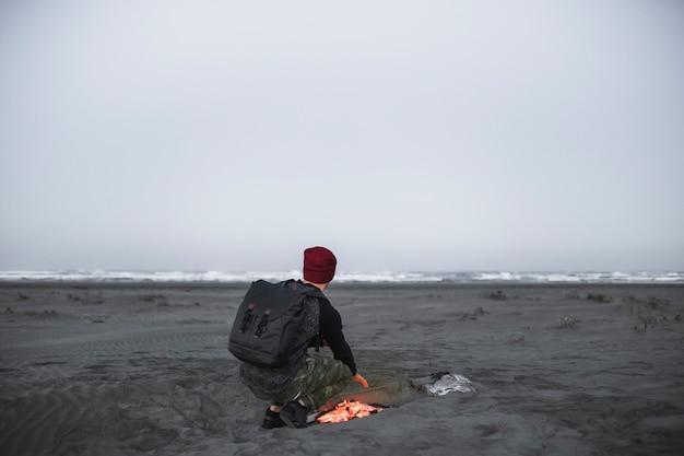 Hombre anónimo que se calienta cerca del fuego Foto gratis