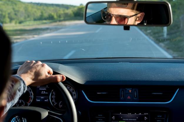 Hombre anónimo viajando con coche en día soleado Foto gratis