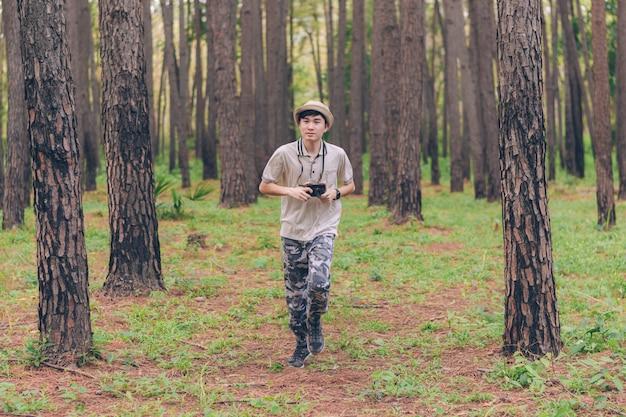 El hombre de asia usa camisa, sombrero y pantalones de camuflaje, corre y toma fotos en el bosque Foto Premium