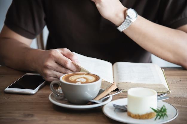 Hombre asiático bebiendo un café y leyendo un libro Foto gratis