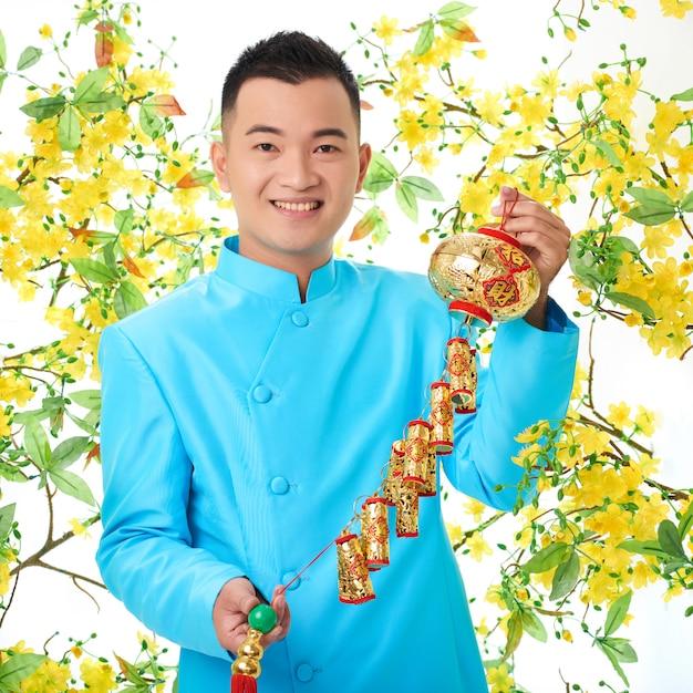 Hombre asiático en chaqueta tradicional posando con linterna colorida, rodeada de flor de mimosa Foto gratis