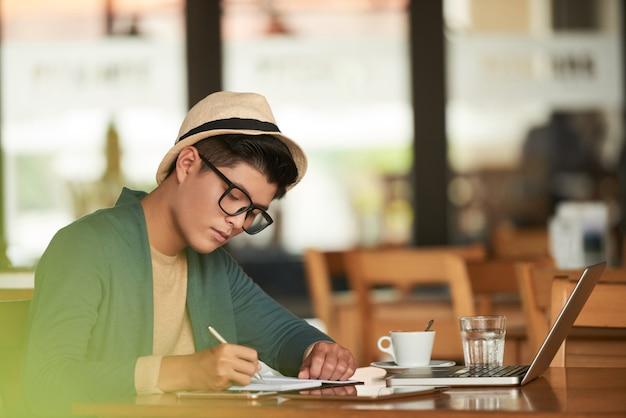 Hombre asiático elegante joven sentado en la cafetería con ordenador portátil y escribir en el cuaderno Foto gratis