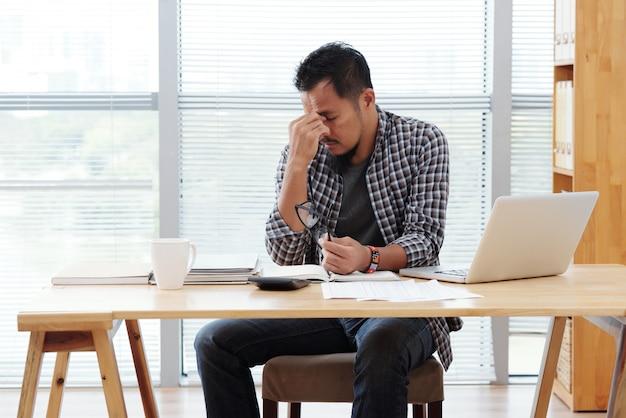 Hombre asiático estresado sentado a la mesa con ordenador portátil y documentos y frotándose la frente Foto gratis