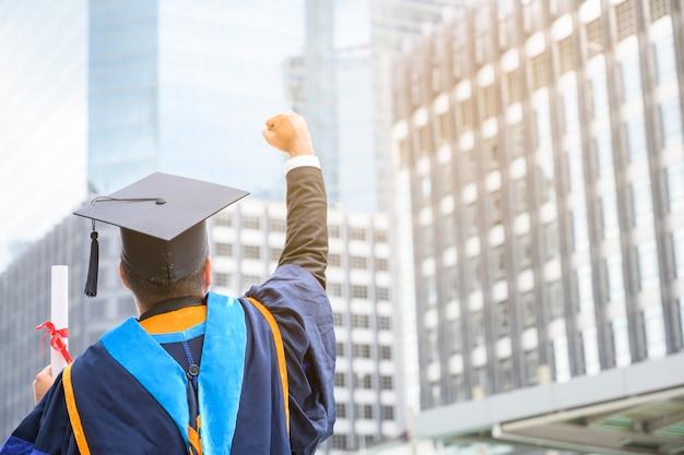 Hombre asiático feliz en vestidos de graduación con diploma en mano en la ciudad urbana. Foto Premium