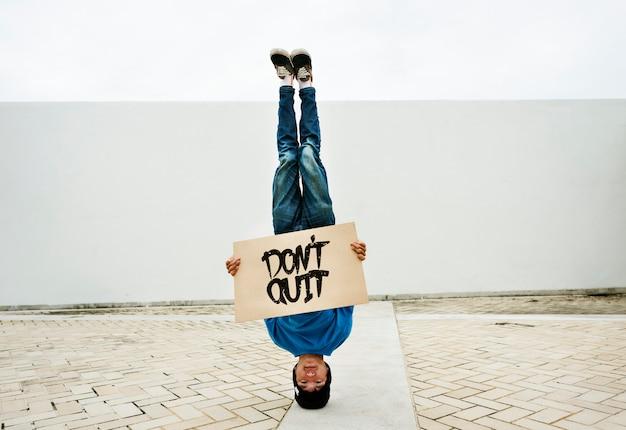 Hombre asiático haciendo una parada de cabeza con una pancarta de no salir Foto gratis