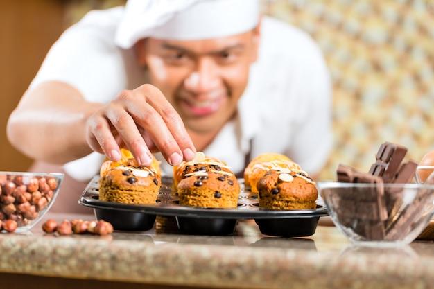 Hombre asiático hornear magdalenas en la cocina de casa Foto Premium