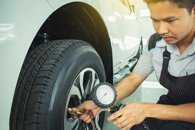 Hombre asiático inspección de automóviles medida de la cantidad de neumáticos de goma inflados ca Foto Premium