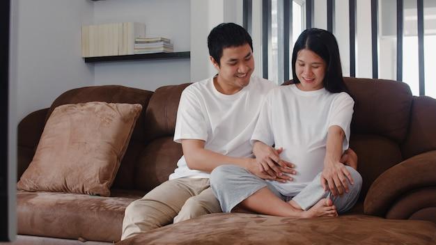 El hombre asiático joven de la pareja embarazada toca el vientre de su esposa hablando con su hijo. mamá y papá se sienten felices sonriendo pacíficos mientras cuidan bebé, embarazo acostado en el sofá en la sala de estar en casa. Foto gratis
