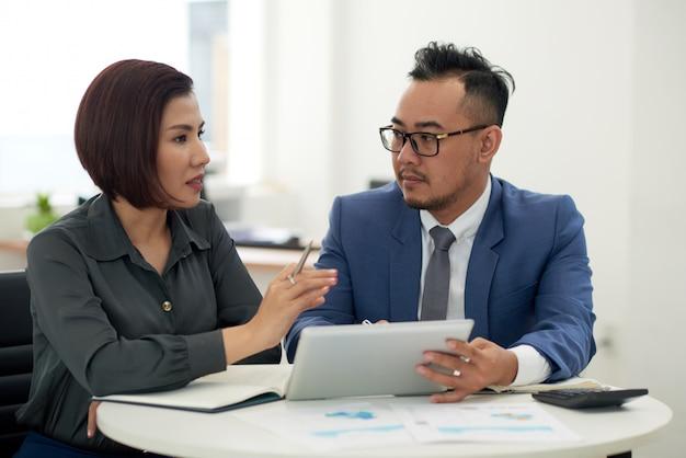Hombre asiático y mujer en traje de negocios sentado en el interior con tableta y hablando Foto gratis