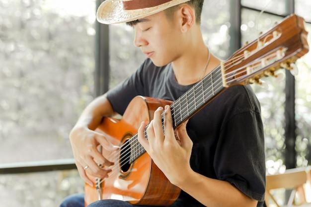 Hombre asiático que toca una guitarra clásica con su ojo cercano. Foto Premium