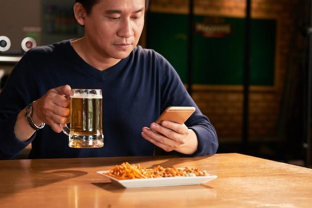Hombre asiático sentado en un pub con cerveza y aperitivos y con smartphone Foto gratis