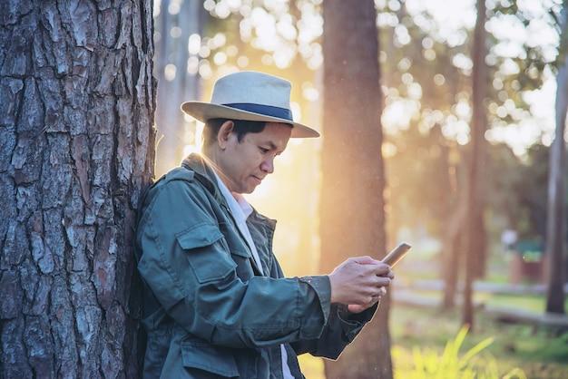 Hombre asiático con el teléfono móvil en la naturaleza del árbol forestal - gente en naturaleza de la primavera y concepto de la tecnología Foto gratis
