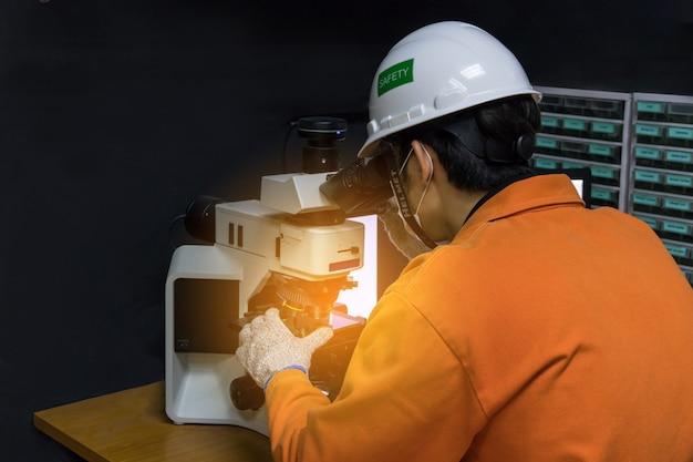Hombre asiático en traje naranja con equipo de seguridad utilizado microscopio de vidrio de calidad en cuarto oscuro de laboratorio de control de calidad Foto Premium